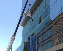 (Part) of a staircase is moved with a crane to a building for assembly. Blue skies in the background.