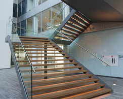 A detached staircase which is composed of matching oak steps, LED lighting and glass railings.