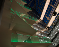 Balconies with green-lighted balustrades and a glass facade.